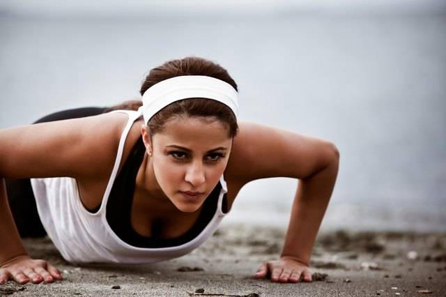 A woman does a pushup on a beach.