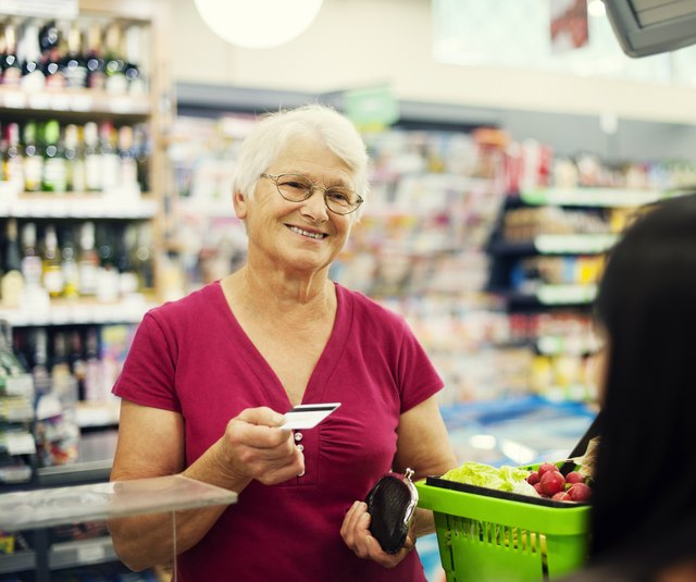 woman handing over credit card at grocery store