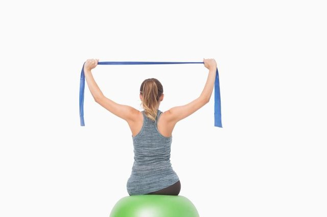 Tone your chest muscles with a stability ball and a resistance band.