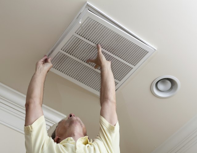 Older man reaching up to replace a air-conditioner filter.