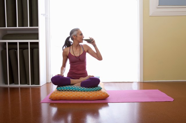 Woman on yoga mat drinking glass of alkaline water.
