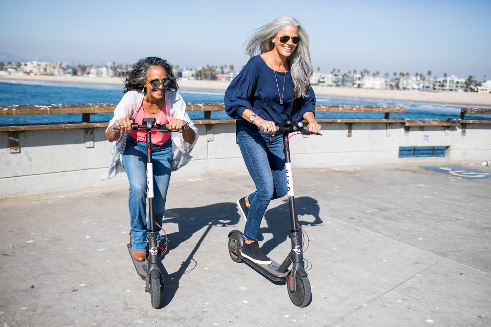 Two women on scooters.